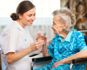 caregiver assisting her patient in drinking